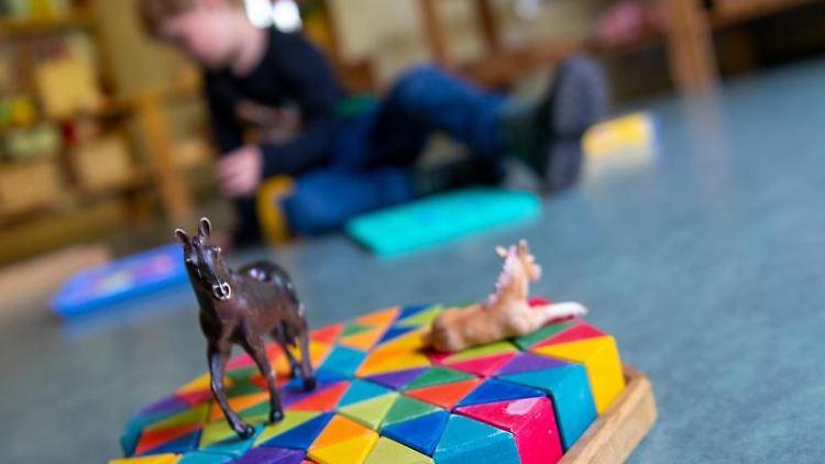 Ein Junge spielt in einem Kindergarten auf dem Boden. Foto: Monika Skolimowska/dpa-Zentralbild/dpa/Symbolbild