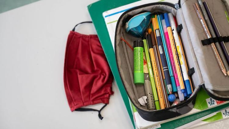 Eine Atemschutzmaske liegt neben einem Federmäppchen. Foto: Marijan Murat/dpa/Symbolbild