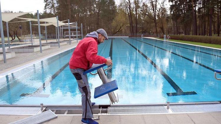 Rene Poppel, Leiter des Freibads Waldfrieden, installiert einen Startblock am Rand des Schwimmbeckens. Foto: Soeren Stache/dpa-Zentralbild/dpa
