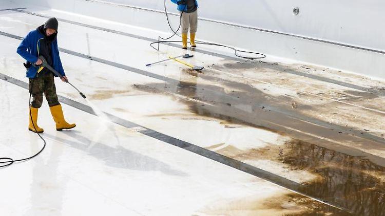 Mitarbeiter derBäder Halle GmbH reinigen ein großes Becken. Foto: Jan Woitas/dpa-Zentralbild/dpa