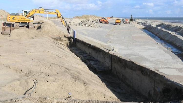 Ein Bagger legt Betonelemente am Norderneyer Westdeich frei. Foto: Volker Bartels/dpa/Archivbild