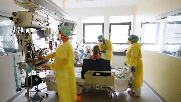 Ärzte und Pfleger untersuchen einen Patienten auf einer Covid-19-Intensivstation. Foto: Bodo Schackow/dpa-zentralbild/dpa/Archivbild