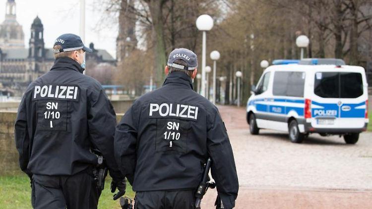 Polizisten gehen vor der Kulisse der Frauenkirche zu einem Einsatzfahrzeug. Foto: Sebastian Kahnert/dpa-Zentralbild/dpa