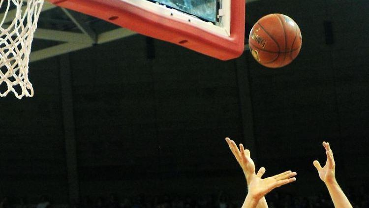 Zwei Basketballspieler kämpfen um den Ball. Foto: picture alliance/Tobias Hase/dpa/Symbolbild