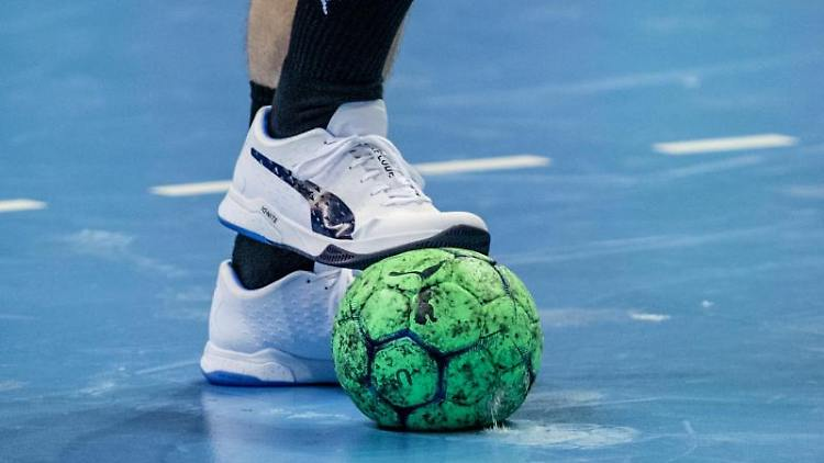 Ein Spieler hält einen Handball mit dem Fuß fest. Foto: Andreas Gora/dpa/Symbolbild