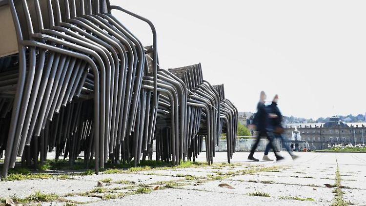 Stühle eines Straßencafes stehen gestapelt auf dem Schlossplatz. Foto: Bernd Weißbrod/dpa/Archivbild