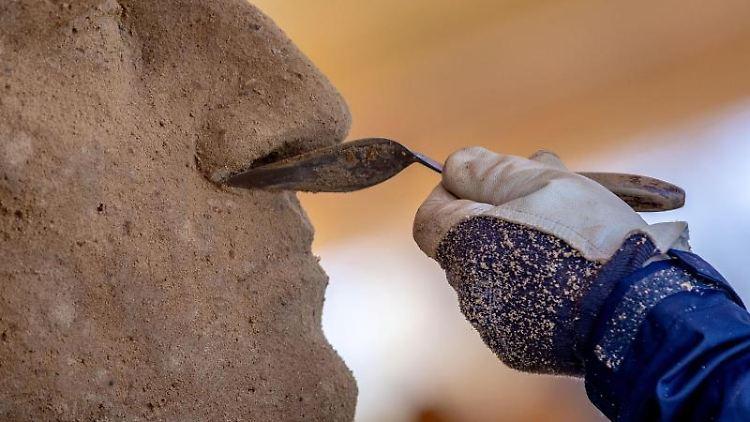 Es wird an einer Skulptur für die 11. Warnemünder Sandwelt gearbeitet. Foto: Jens Büttner/dpa-Zentralbild/dpa