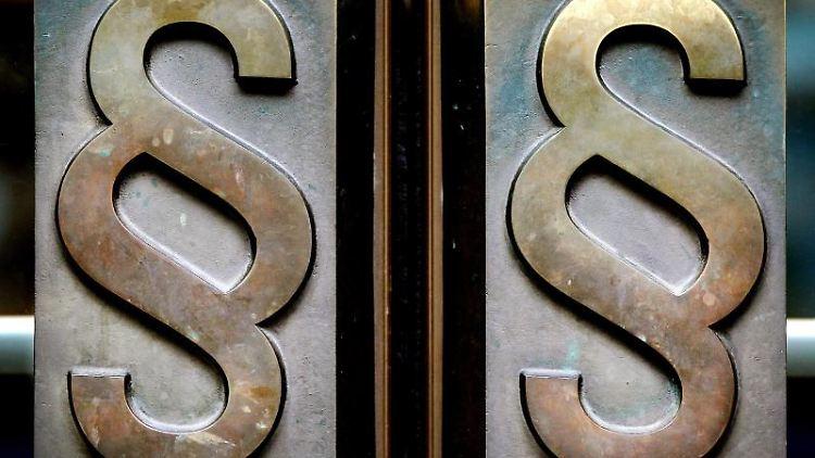 Paragrafen-Symbole sind an Türgriffen am Eingang eines Landgerichts angebracht. Foto: Oliver Berg/dpa/Symbolbild