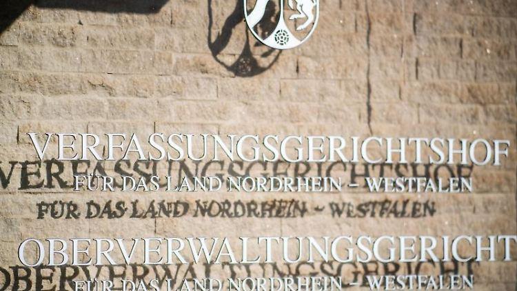 An der Aussenfassade am OVG hängt eine Hinweistafel mit dem Landeswappen von NRW und den Schriftzügen:
