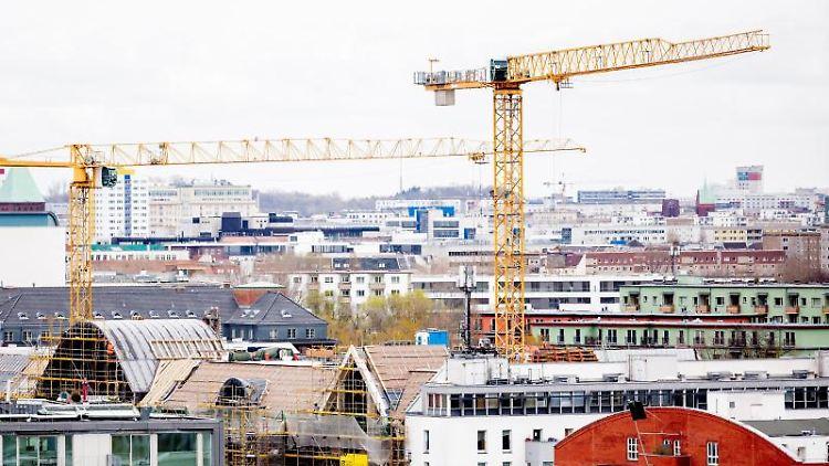 Baukräne ragen zwischen Gebäuden hervor.. Foto: Christoph Soeder/dpa/Symbolbild