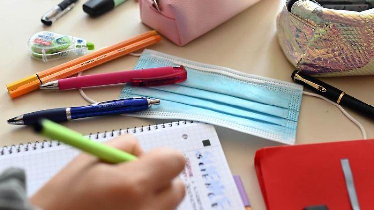 Während einer Unterrichtsstunde liegt ein Mund-Nasen-Schutz auf dem Tisch einer Schülerin. Foto: Uli Deck/dpa/Archivbild