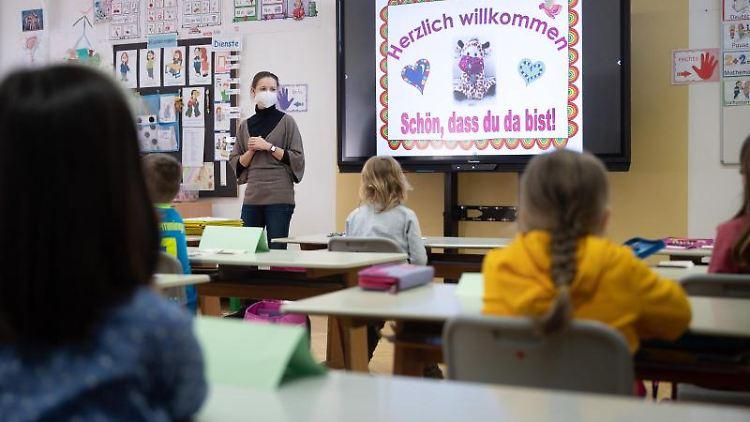 Eine Lehrerin mit FFP2-Maske unterrichtet in einer ersten Klasse. Foto: Sebastian Gollnow/dpa/Symbolbild