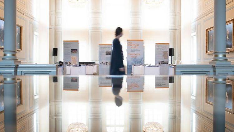 """Eine Mitarbeiterin geht im Sorbischen Museum Bautzen durch die Ausstellung """"Die Freiheit winkt! Die Sorben und die Minderheitenfrage nach 1918"""" und spiegelt sich in einer Glasvitrine. Foto: Sebastian Kahnert/dpa-Zentralbild/dpa"""