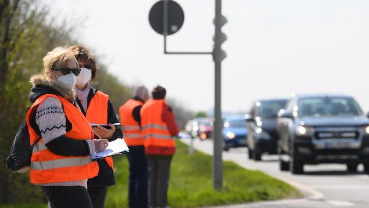 Verkehrszählerinnen stehen im Rahmen der Straßenverkehrszählung 2021 an einer Bundesstraße und tragen vorbeifahrende Autos nach Typ in eine Liste ein. Foto: Robert Michael/dpa-Zentralbild/dpa