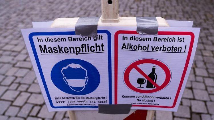 Ein Schild weist auf die Maskenpflicht und das Alkoholverbot hin. Foto: Nicolas Armer/dpa/Symbolbild