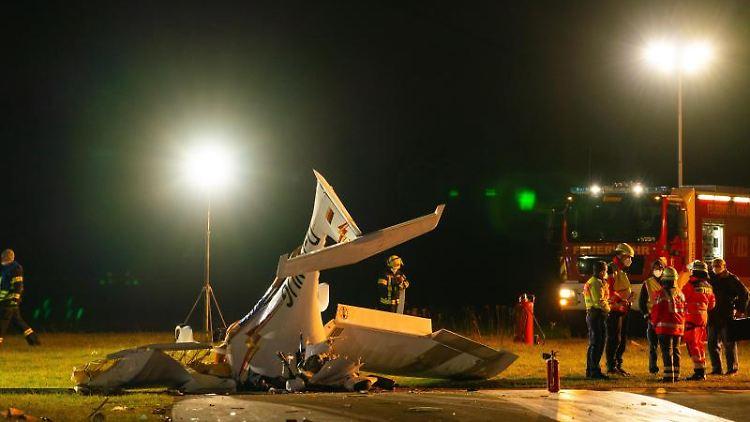 Einsatzkräfte stehen neben einem abgestürzten Sportflugzeug auf dem Rollfeld des Flugplatzes in Kulmbach. Foto: Nicolas Armer/dpa