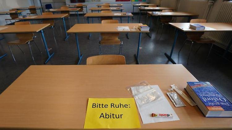 """Ein Zettel mit """"Bitte Ruhe: Abitur"""", ein Corona-Schnelltest, ein Riegel und Englisch-Wörterbuch. Foto: Marcus Brandt/dpa"""