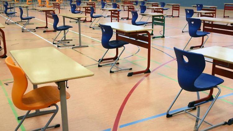 Mit großen Abständen stehen Tische und Stühle in der Turnhalle. Foto: Waltraud Grubitzsch/dpa-Zentralbild/dpa/Archivbild
