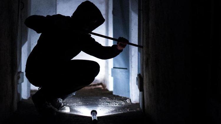 Ein fiktiver Einbrecher hebelt mit einem Brecheisen eine Tür im Keller eines Wohnhauses auf (gestellte Szene). Foto: Silas Stein/dpa/Archivbild