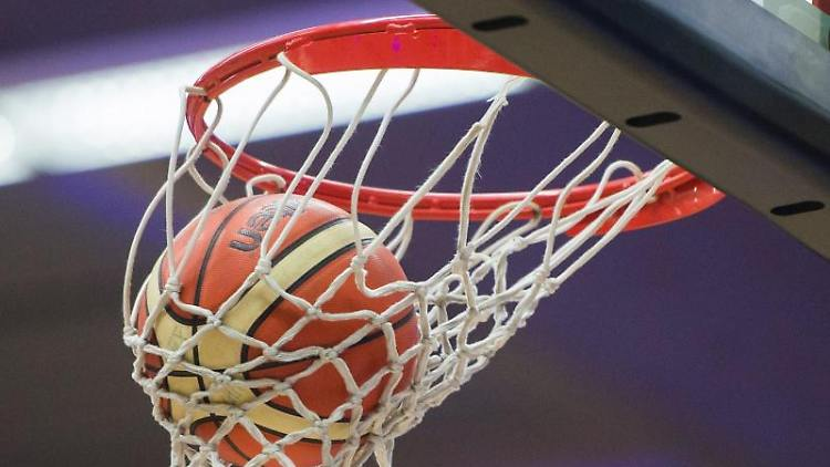 Ein Basketball im Korb. Foto: Lukas Schulze/picture alliance/dpa/Symbolbild