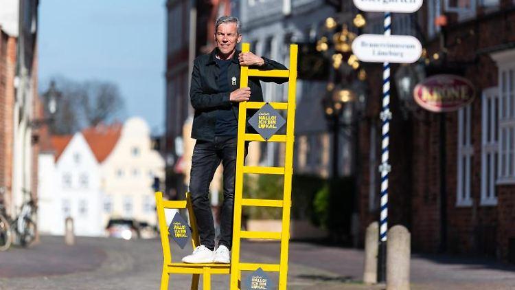 Ralf Elfers, Ideengeber und Ladenbesitzer, steht mit einer gelben Leiter und einem gelben Stuhl in der Innenstadt. Foto: Philipp Schulze/dpa