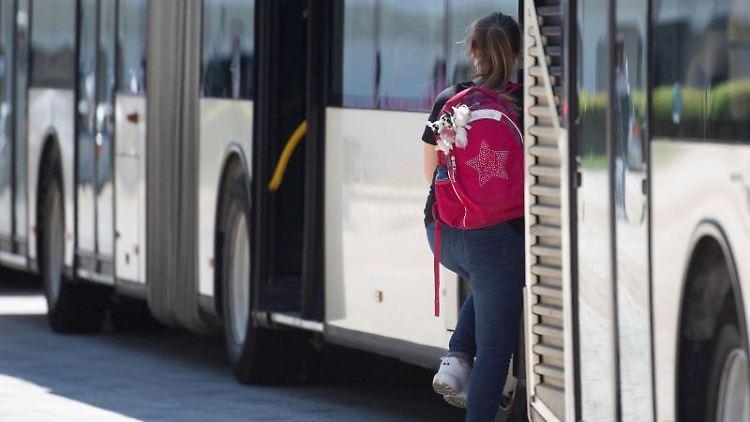 Eine Schülerin steigt in einen Bus ein. Foto: Marijan Murat/dpa/Archivbild