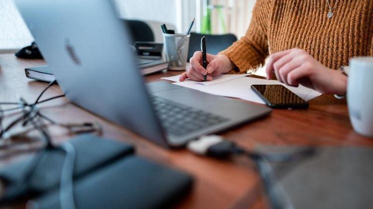 Eine Frau sitzt mit einem Laptop an einem Tisch im Homeoffice. Foto: Fabian Strauch/dpa/Symbolbild