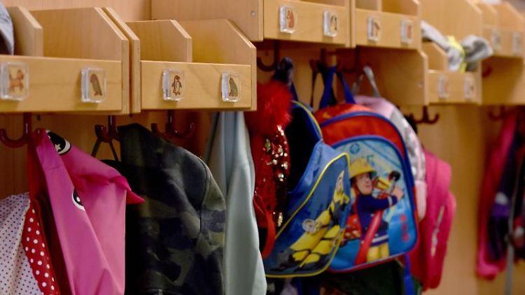 Jacken und Rucksäcke hängen in einer Städtischen Kita an Haken im Flur. Foto: Caroline Seidel/dpa