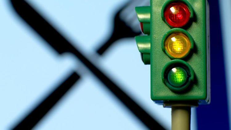 Eine Spielzeugampel leuchtet vor einem Restaurant-Logo. Foto: Jens Büttner/dpa/Illustration