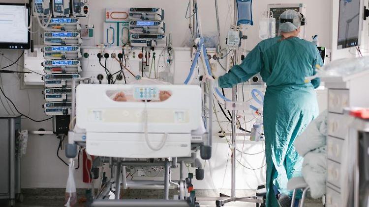 Eine Intensivpflegerin versorgt auf der Intensivstation einen Patienten. Foto: Ole Spata/dpa