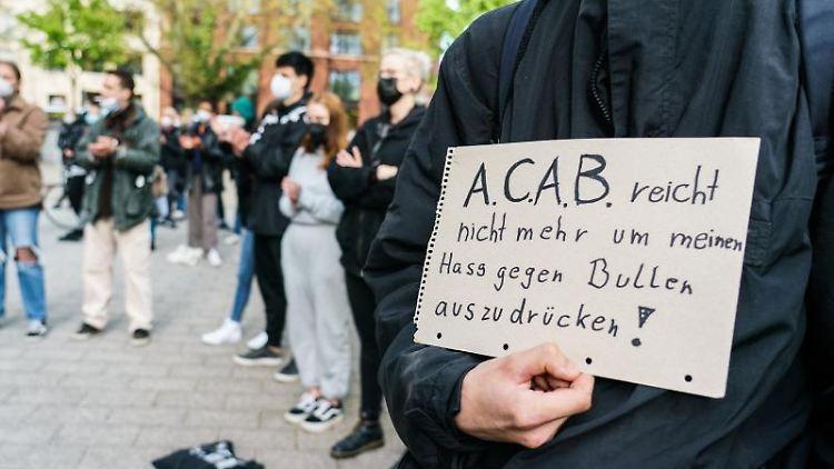 Ein Kundgebungsteilnehmer hält ein Plakat in seiner Hand. Foto: Andreas Arnold/dpa