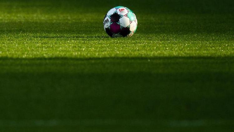 Ein Ball liegt auf dem Rasen. Foto: Julian Stratenschulte/dpa/Symbolbild