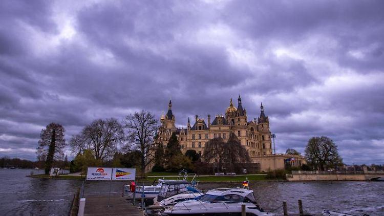 Dunkle Regenwolken ziehen über das Schweriner Schloss. Foto: Jens Büttner/dpa-Zentralbild/dpa