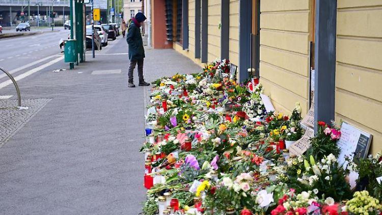 Eine Frau betrachtet vor der Einrichtung Oberlinhaus die Blumen und Beileidsbekundungen. Foto: Soeren Stache/dpa-Zentralbild/dpa