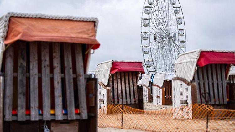 Ein Riesenrad steht hinter Strandkörben am Strand von Schillig. Foto: Sina Schuldt/dpa