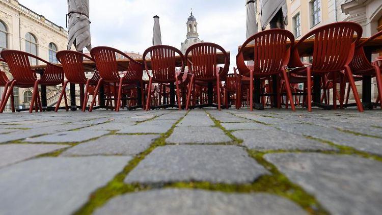 Tische und Stühle sind in Dresden vor einem Restaurant auf dem Neumarkt aufgestellt. Foto: Robert Michael/dpa-Zentralbild/dpa/Archivbild
