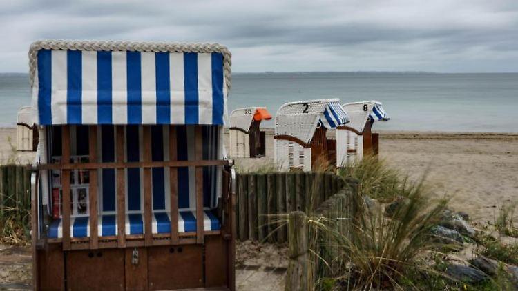 Regenwolken ziehen über die Lübecker Bucht und die Strandkörbe am Timmendorfer Strand. Foto: Axel Heimken/dpa