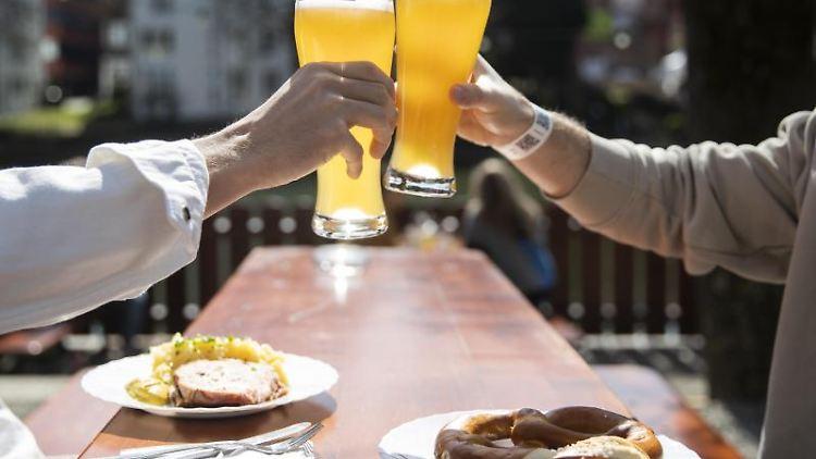 Zwei Menschen sitzen bei gutem Wetter in einem Biergarten. Foto: Tom Weller/dpa/Symbolbild