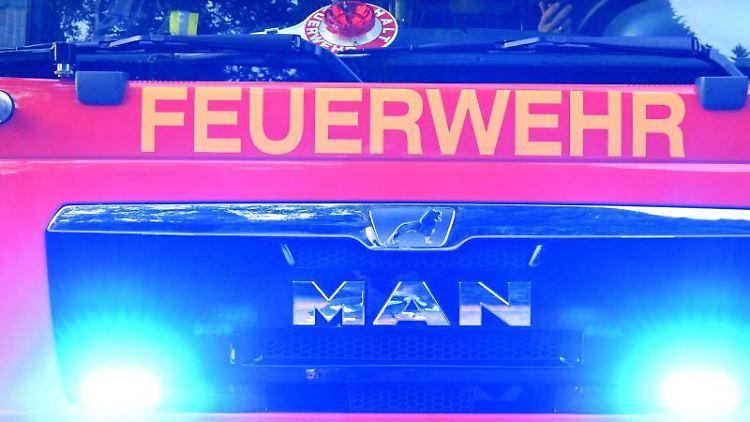 Feuerwehrmänner sitzen in ihrem Fahrzeug. Foto: Carsten Rehder/dpa