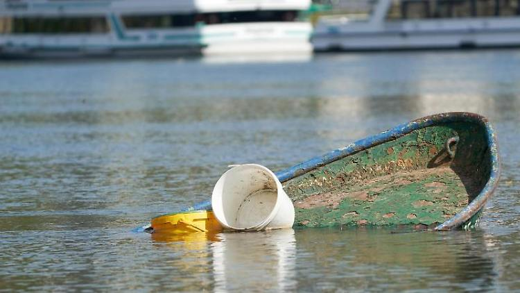 Ein versunkenes Ruderboot liegt am Ufer der Rheininsel Niederwerth. Foto: Thomas Frey/dpa