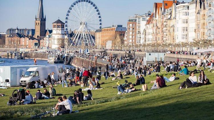 Zahlreiche Menschen sitzen bei sommerlichen Temperaturen und Sonnenschein auf der Rheinpromenade. Foto: Marcel Kusch/dpa/Symbolbild