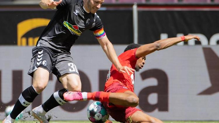 Kölns Kingsley Ehizibue (r) und Freiburgs Christian Günter versuchen an den Ball zu kommen. Foto: Rolf Vennenbernd/dpa
