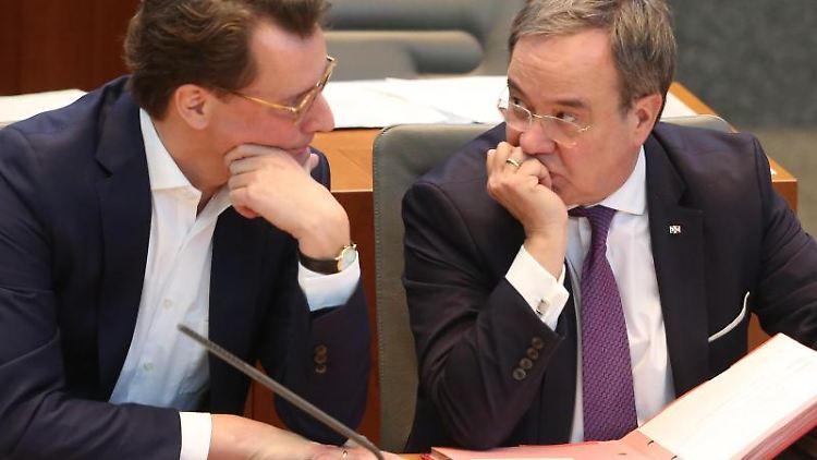 Der nordrhein-westfälische Verkehrsminister Hendrik Wüst (CDU, l) spricht mit Ministerpräsident Armin Laschet (CDU). Foto: Roland Weihrauch/dpa/Archivbild