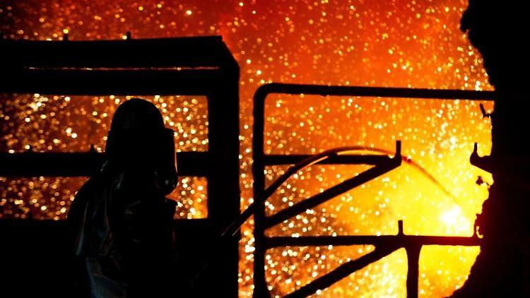 Ein Mitarbeiter reinigt im Stahlwerk der Salzgitter AG eine Roheisenpfanne. Foto: Hauke-Christian Dittrich/dpa/Archivbild