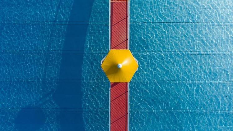 Ein roter Steg mit einem gelben Schirm überspannt ein noch menschenleeres Freibad. Foto: Boris Roessler/dpa