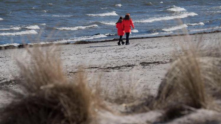 Spaziergänger gehen am Strand im Ostseebad Binz auf der Insel Rügen. Foto: Stefan Sauer/dpa-Zentralbild/ZB/archivbild