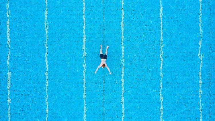 Ein Gast zieht im Freibad schwimmend seine Bahnen. Foto: Guido Kirchner/dpa