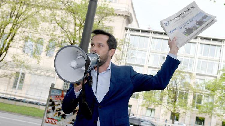 Martin Hagen (FDP), Fraktionsvorsitzender im Bayerischen Landtag, spricht in ein Megafon. Foto: Felix Hörhager/dpa