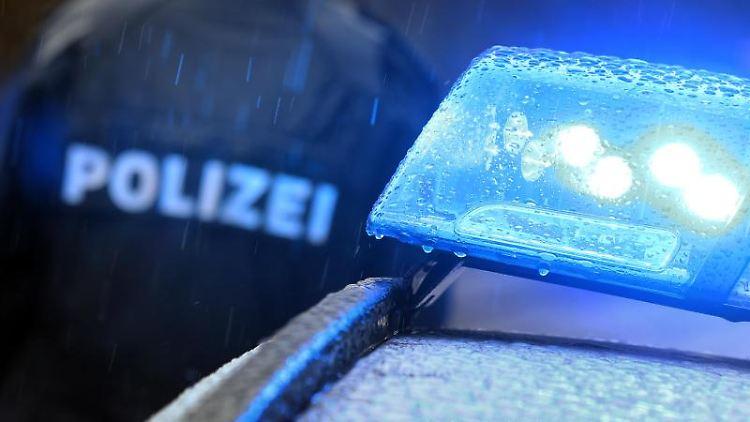 Ein Polizist steht im Regen vor einem Streifenwagen dessen Blaulicht aktiviert ist. Foto: Karl-Josef Hildenbrand/dpa/Symbol