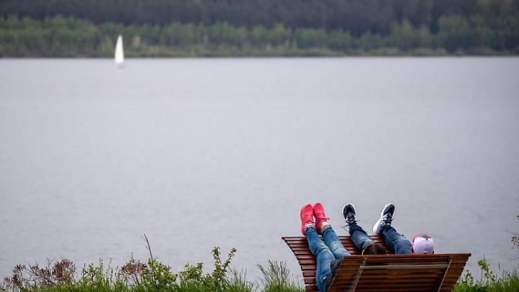 Zwei Ausflügler verweilen am Vatertag an einemSee. Foto: Daniel Karmann/dpa/Symbolbild